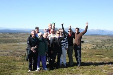 Voksne Burn Camp deltakere som jubler på toppen av et fjell.